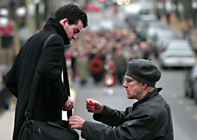 A veteran pins a poppy on a McGill student's bag